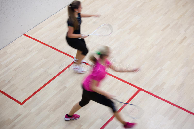 Δύο θηλυκοί φορείς κολοκύνθης στη γρήγορη δράση σε ένα γήπεδο squash στοκ φωτογραφία με δικαίωμα ελεύθερης χρήσης