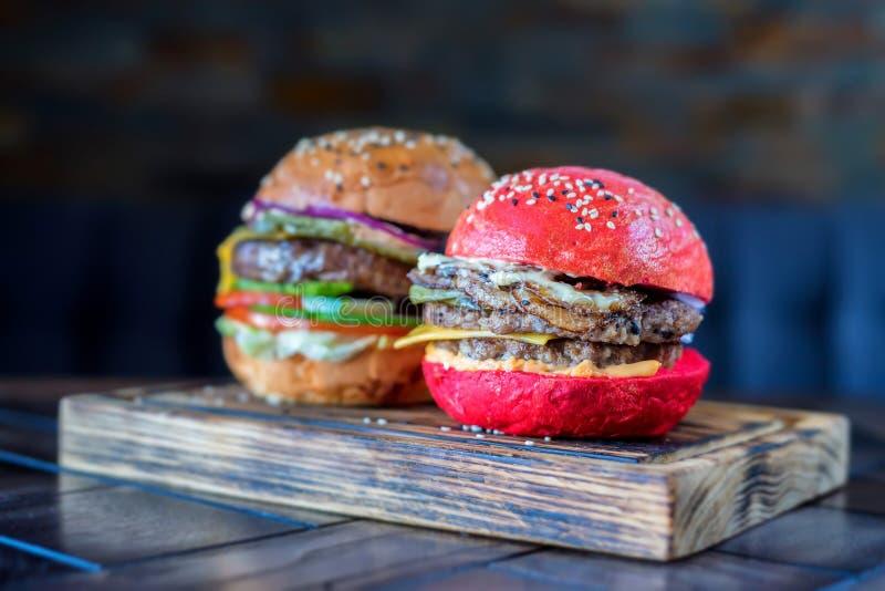Δύο διαφορετικά burgers εστιατορίων στον ξύλινο πίνακα στοκ εικόνες