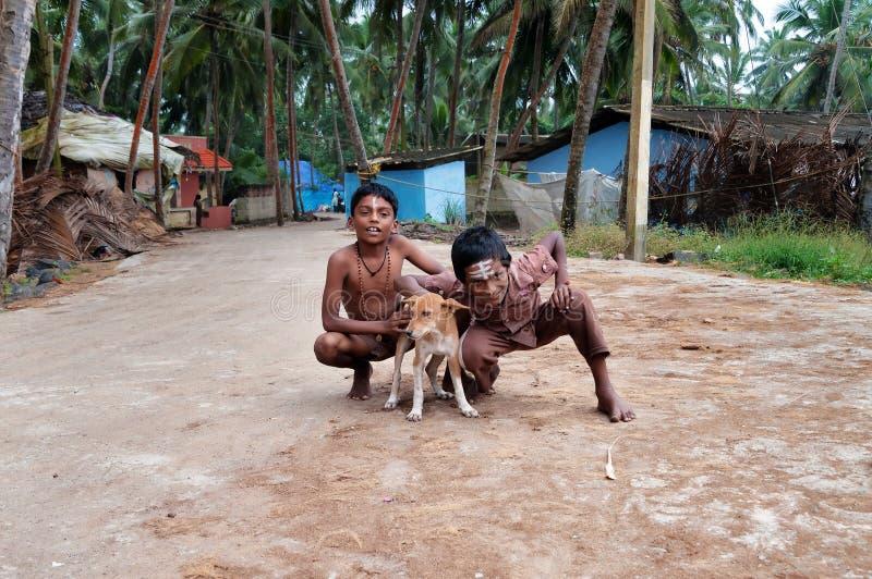 Δύο ινδικά αγόρια με το σκυλί στην οδό στο ψαροχώρι στοκ εικόνες