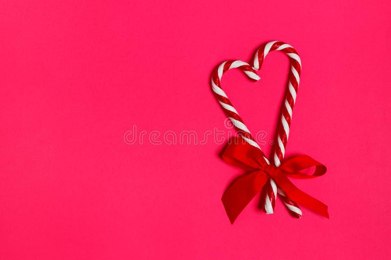 Δύο κάλαμοι καραμελών Χριστουγέννων που επικαλύπτουν για να διαμορφώσουν μια καρδιά και ένα κόκκινο υποκύπτουν σε ένα ρόδινο υπόβ στοκ εικόνες με δικαίωμα ελεύθερης χρήσης