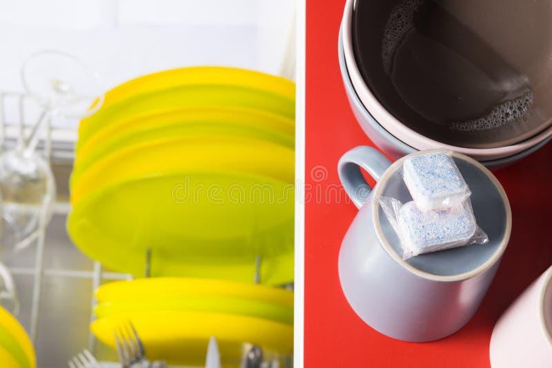 Δύο κάψες για τον καθαρισμό από το λίπος, βρίσκονται στις βρώμικες κούπες, στον πίνακα, πρίν φορτώνουν στο πλυντήριο πιάτων στοκ εικόνες