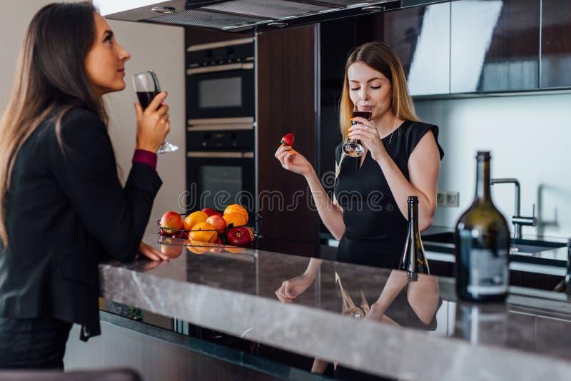 Δύο καλύτεροι φίλοι που έχουν ένα λίγο κόμμα εγκαίνιας σπιτιού με την κατανάλωση του κόκκινου κρασιού που στέκεται στην κουζίνα στοκ εικόνες