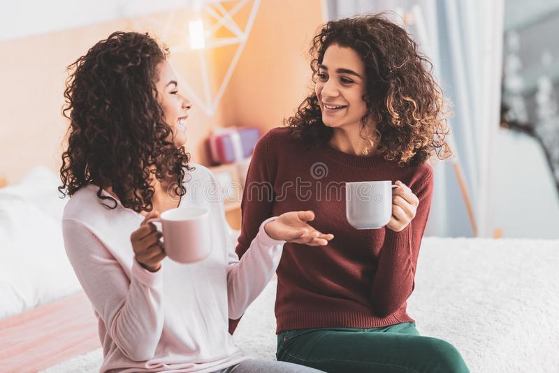 Δύο καλύτεροι φίλοι που κουτσομπολεύουν ενώ έχοντας το χρόνο τσαγιού στοκ εικόνες