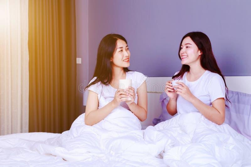 Δύο καλύτεροι φίλοι που μιλούν και που πίνουν ένα φλιτζάνι του καφέ στο κρεβάτι μέσα στοκ εικόνα