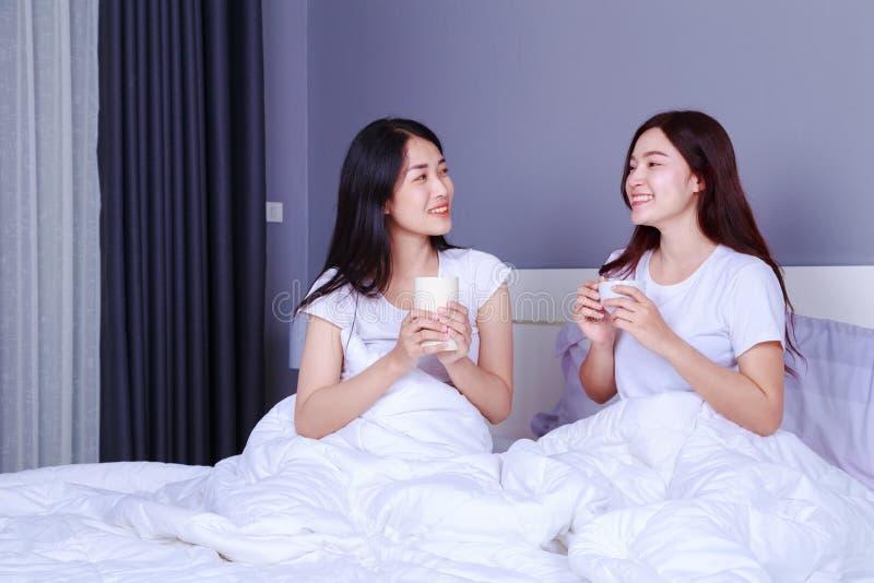 Δύο καλύτεροι φίλοι που μιλούν και που πίνουν ένα φλιτζάνι του καφέ στο κρεβάτι μέσα στοκ εικόνες