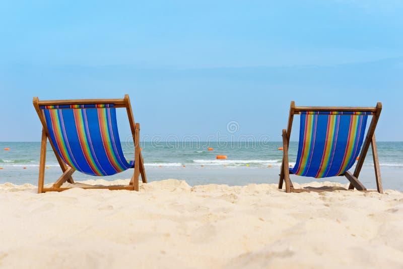 Δύο καρέκλες καμβά στο υπόβαθρο παραλιών Στην άσπρη άμμο και την μπλε θάλασσα τόσο όμορφες και χαλαρώστε την άποψη στοκ φωτογραφία με δικαίωμα ελεύθερης χρήσης