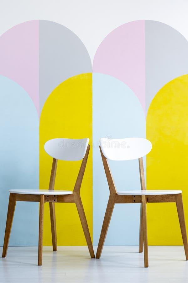 Δύο καρέκλες που τίθενται σε έναν διαμορφωμένο τοίχο με τις κίτρινες εμφάσεις σε φωτεινό στοκ εικόνες με δικαίωμα ελεύθερης χρήσης