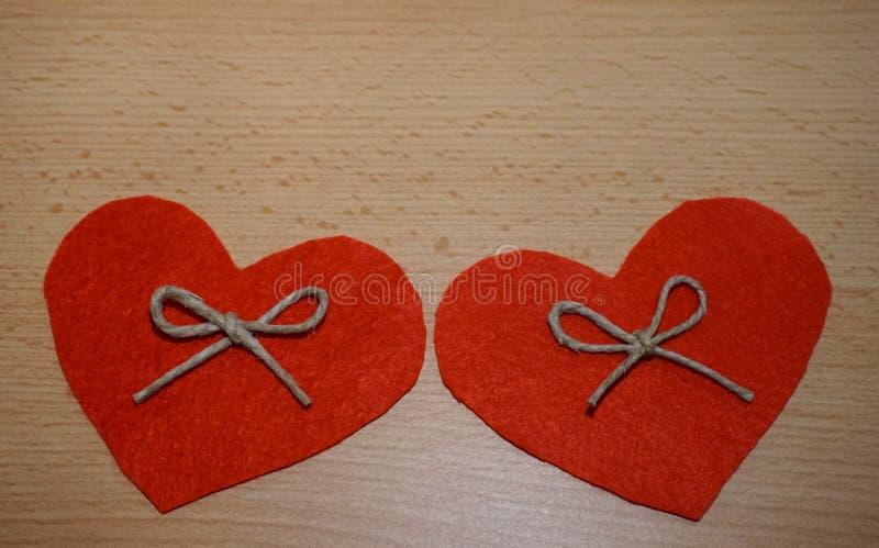Δύο καρδιές που γίνονται από το φυσικό υλικό στο ξύλινο υπόβαθρο με το ελεύθερο διάστημα αντιγράφων στοκ φωτογραφίες