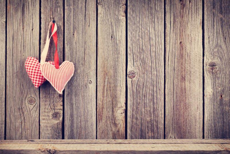 Δύο καρδιές ημέρας βαλεντίνων στον αγροτικό ξύλινο τοίχο
