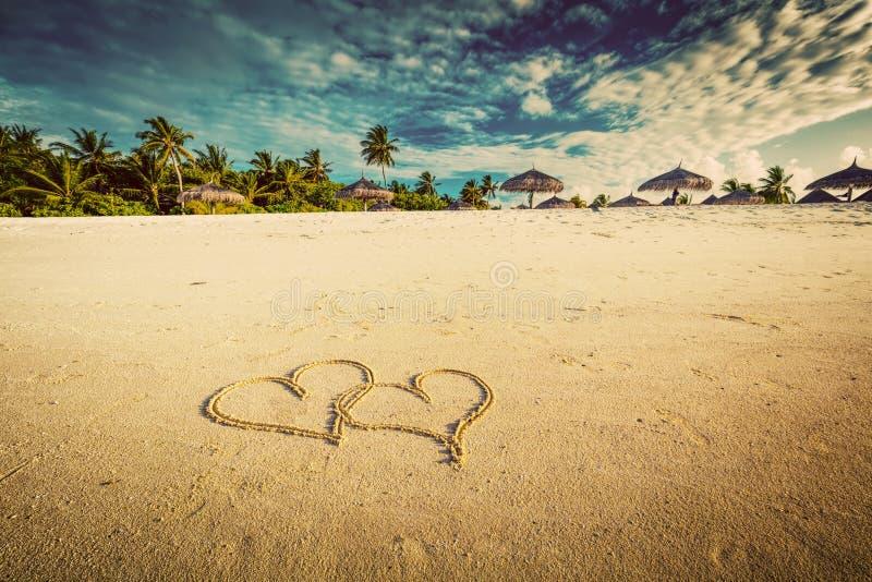 Δύο καρδιές που επισύρονται την προσοχή στην άμμο μιας τροπικής παραλίας Τρύγος στοκ εικόνες με δικαίωμα ελεύθερης χρήσης