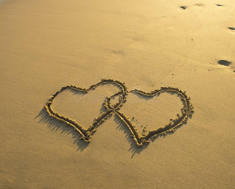 Δύο καρδιές που σύρονται στην παραλία στοκ εικόνα με δικαίωμα ελεύθερης χρήσης
