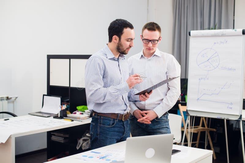 Δύο καυκάσιοι διοικητικοί συνεργάτες στην περιστασιακή ένδυση που διοργανώνει μια επιχειρησιακή συζήτηση στην αρχή στοκ εικόνα