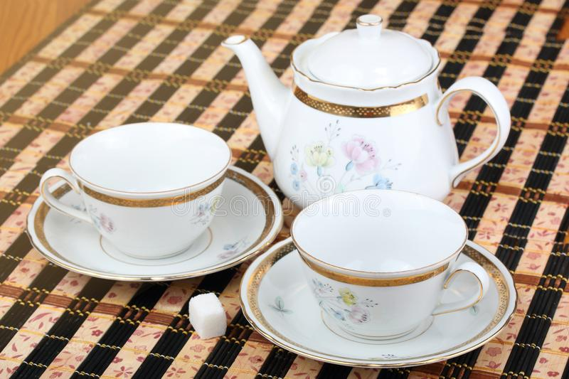 Δύο κενά άσπρα φλυτζάνι και teapot πορσελάνης στον πίνακα που καλύπτεται με το ριγωτό επιτραπέζιο χαλί στοκ εικόνα με δικαίωμα ελεύθερης χρήσης