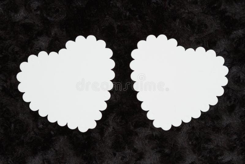 Δύο κενές άσπρες καρδιές στο Μαύρο αυξήθηκαν κατασκευασμένο ύφασμα βελούδου στοκ φωτογραφίες