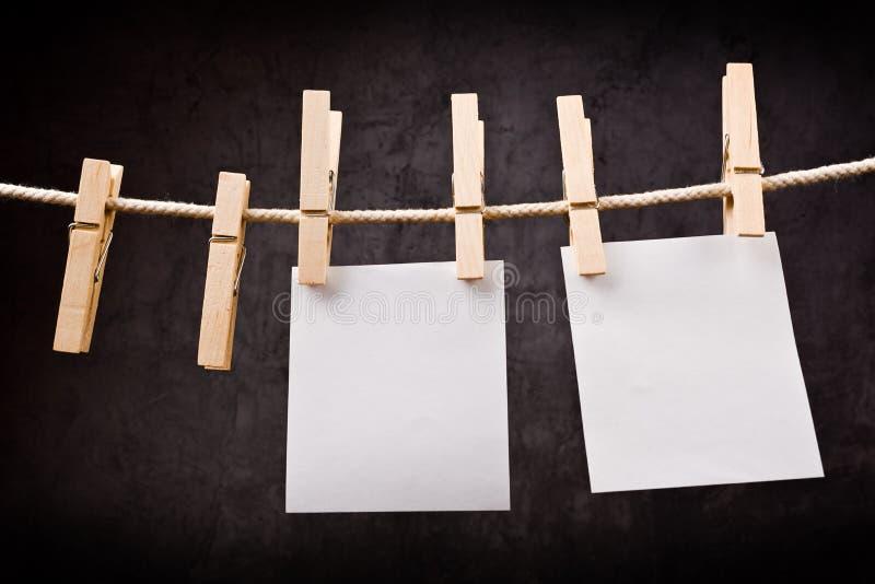 Δύο κενές σημειώσεις εγγράφου που κρεμούν στο σχοινί με τις καρφίτσες ενδυμάτων στοκ εικόνα με δικαίωμα ελεύθερης χρήσης