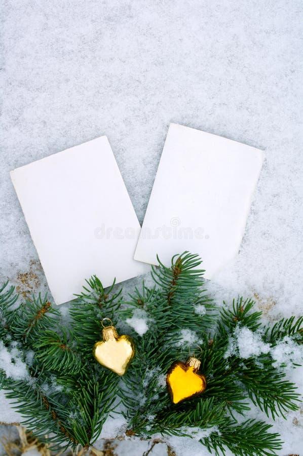Δύο κενές φωτογραφίες ενός κλάδου fir-tree και του νέου έτους των παιχνιδιών στο χιόνι στοκ φωτογραφία
