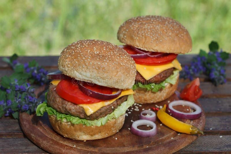 Δύο κλασικά cheeseburgers στον ξύλινο πίνακα στοκ φωτογραφίες με δικαίωμα ελεύθερης χρήσης