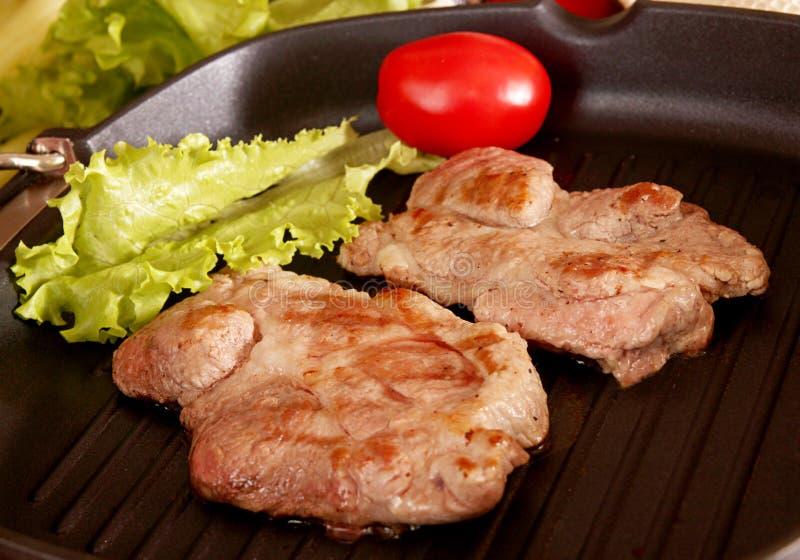 Δύο κομμάτια των ψημένων στη σχάρα μπριζολών χοιρινού κρέατος στο τηγάνισμα του τηγανιού σχαρών στοκ φωτογραφίες με δικαίωμα ελεύθερης χρήσης