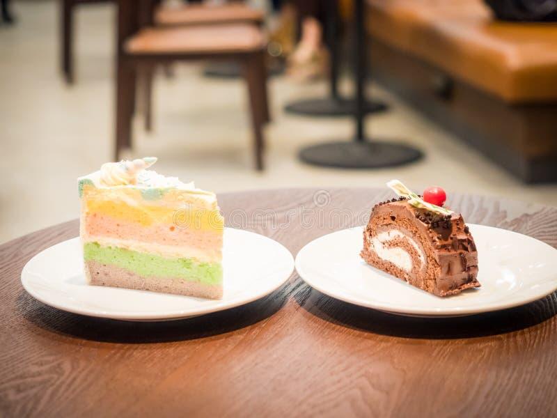 Δύο κομμάτι ομορφιάς του κέικ εξυπηρετεί στο άσπρο πιάτο και έβαλε στο ξύλινο τ στοκ φωτογραφία