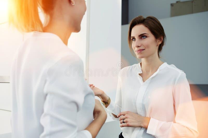 Δύο κομψοί επιχειρηματίες γυναικών που μιλούν για κάτι στεμένος στο σύγχρονο εσωτερικό γραφείων, στοκ εικόνα με δικαίωμα ελεύθερης χρήσης