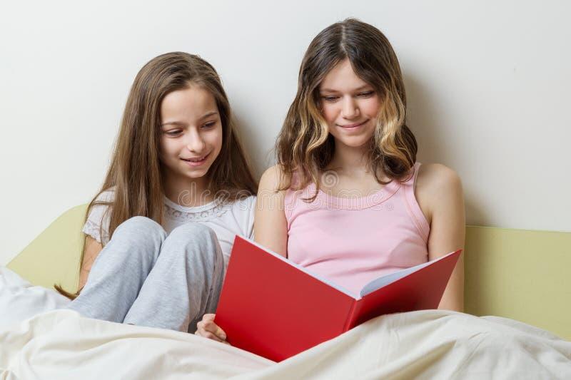 Δύο κορίτσια αδελφών που κάθονται στο σπίτι στο κρεβάτι με μια ανάγνωση σχολικών σημειωματάριων και που μελετούν να προετοιμαστεί στοκ εικόνα με δικαίωμα ελεύθερης χρήσης