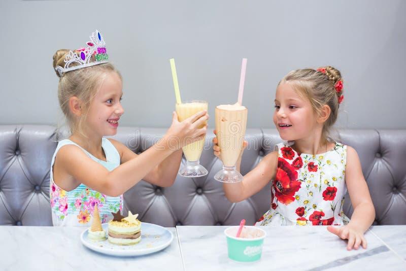 Δύο κορίτσια γιορτάζουν τα γενέθλιά τους Διακοπές παιδιών Μεταχειρίζεται το γλυκό, το κέικ και το χυμό στον πίνακα στοκ φωτογραφίες