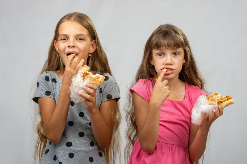 Δύο κορίτσια είναι αστεία τρώγοντας το ψωμί, που ωθεί τα τρόφιμα στο στόμα σας με τα δάχτυλά σας στοκ φωτογραφίες με δικαίωμα ελεύθερης χρήσης