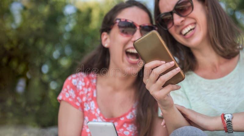 Δύο κορίτσια εκπλήσσουν τα μέσα κοινωνικής δικτύωσης απρόσμενη νεολαία για χιλιετίες φιλία στα μέσα ενημέρωσης για εθισμό στις τά στοκ φωτογραφία