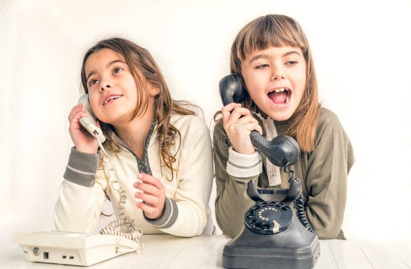 Δύο κορίτσια επτάχρονων παιδιών που μιλούν στα παλαιά εκλεκτής ποιότητας τηλέφωνα με στοκ φωτογραφίες με δικαίωμα ελεύθερης χρήσης