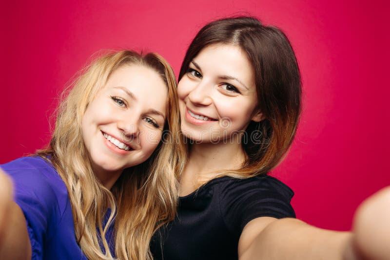 Δύο κορίτσια θετικής σκέψης που παίρνουν το χαμόγελο αυτοπροσωπογραφίας, που θέτει στο ρόδινο υπόβαθρο στοκ φωτογραφία με δικαίωμα ελεύθερης χρήσης