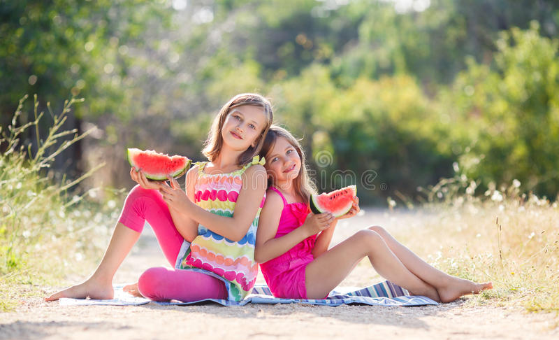 Δύο κορίτσια και ένα juicy κόκκινο καρπούζι στοκ εικόνα με δικαίωμα ελεύθερης χρήσης
