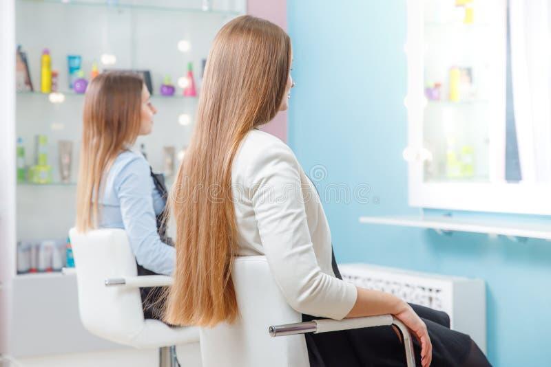 Δύο κορίτσια με την πολύ παχιά καλά-καλλωπισμένη τρίχα κάθονται την καρέκλα στο σαλόνι ομορφιάς, αναμονή στοκ εικόνες