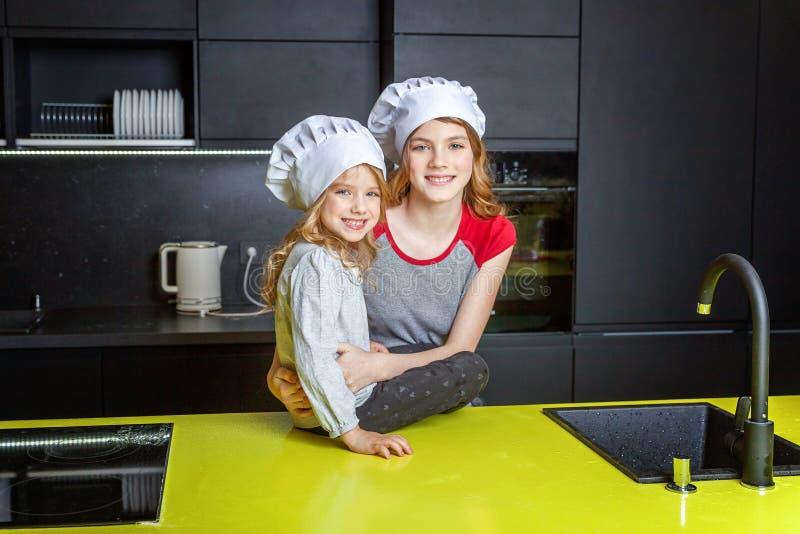 Δύο κορίτσια με το καπέλο αρχιμαγείρων που αγκαλιάζει και που έχει τη διασκέδαση στην κουζίνα στοκ φωτογραφία