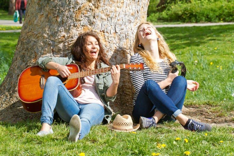 Δύο κορίτσια που έχουν τη διασκέδαση με τα όργανά της στοκ εικόνες
