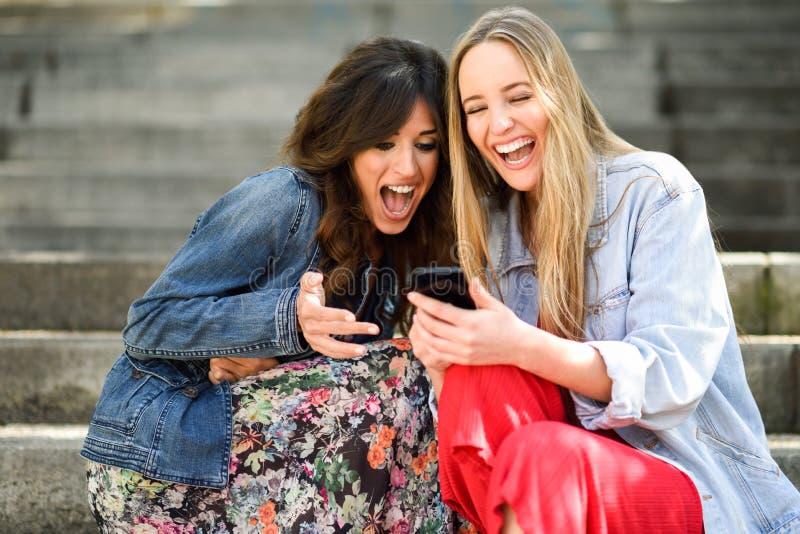 Δύο κορίτσια που εξετάζουν κάποιο αστείο πράγμα στο έξυπνο τηλέφωνό τους στοκ εικόνες