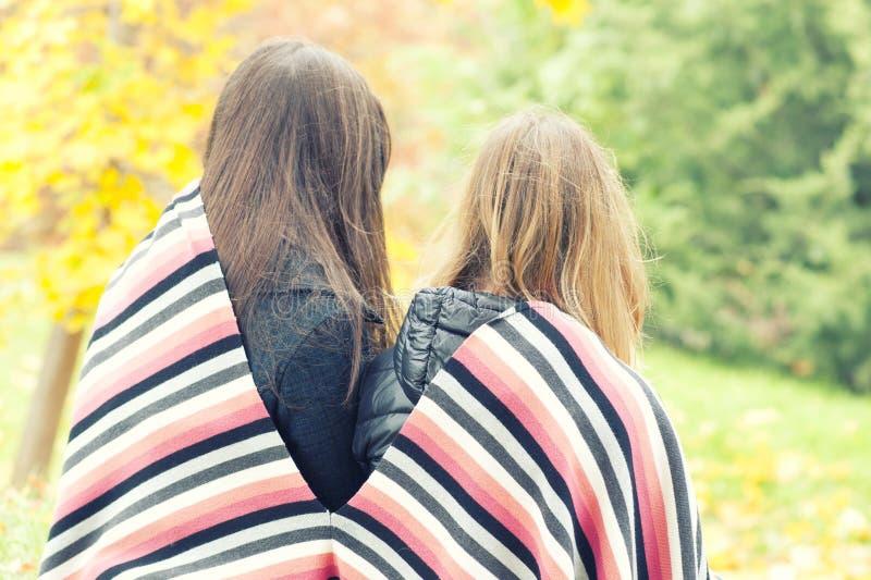 Δύο κορίτσια που κάθονται καλύπτουν σε ένα καρό σε ένα πάρκο φθινοπώρου, στοκ εικόνες