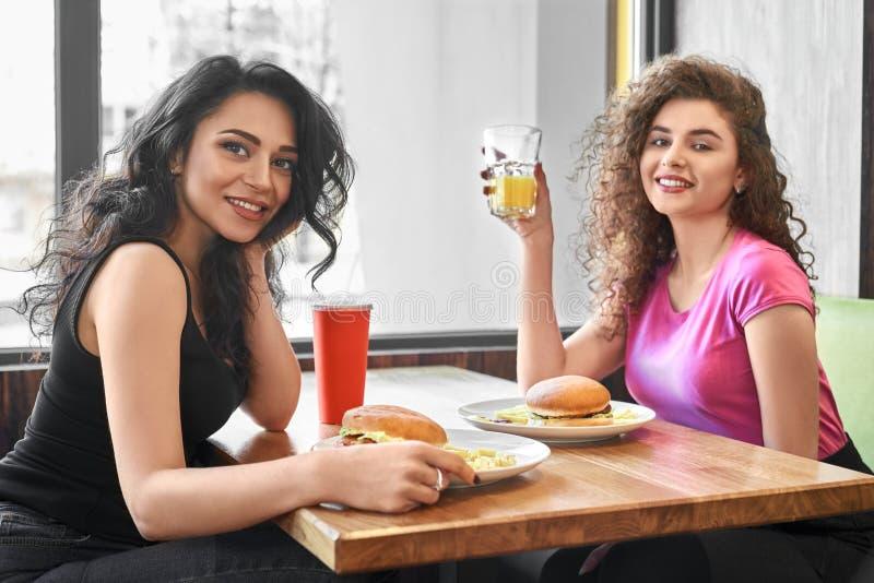 Δύο κορίτσια που κάθονται στον καφέ κοντά στο παράθυρο, που τρώει το γρήγορο φαγητό στοκ εικόνες