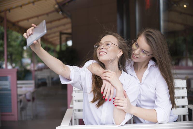 Δύο κορίτσια που κάνουν ένα selfie στο θερινό καφέ στοκ εικόνες με δικαίωμα ελεύθερης χρήσης