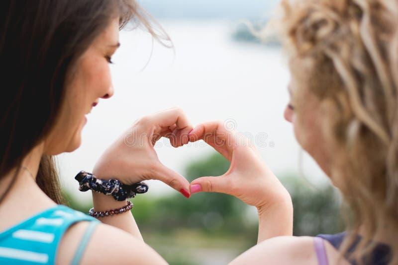 Δύο κορίτσια που κάνουν τη μορφή καρδιών στοκ φωτογραφία