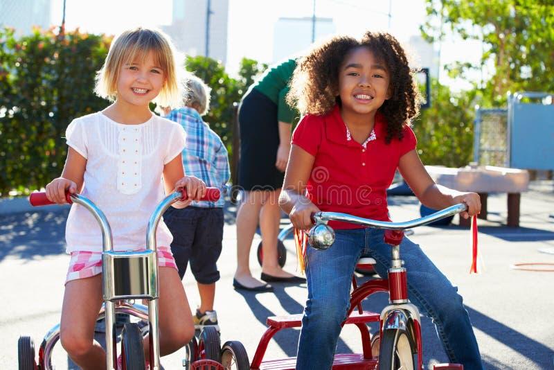 Δύο κορίτσια που οδηγούν τα τρίκυκλα στην παιδική χαρά στοκ εικόνες