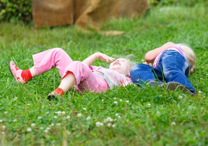 Δύο κορίτσια που παίζουν στην πράσινη χλόη στοκ εικόνες