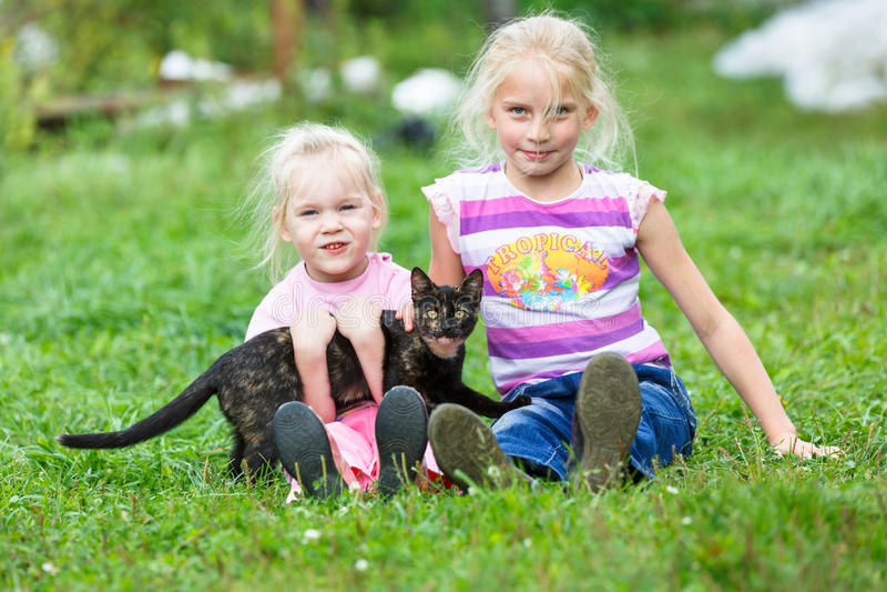 Δύο κορίτσια που παίζουν στην πράσινη χλόη στοκ φωτογραφία με δικαίωμα ελεύθερης χρήσης