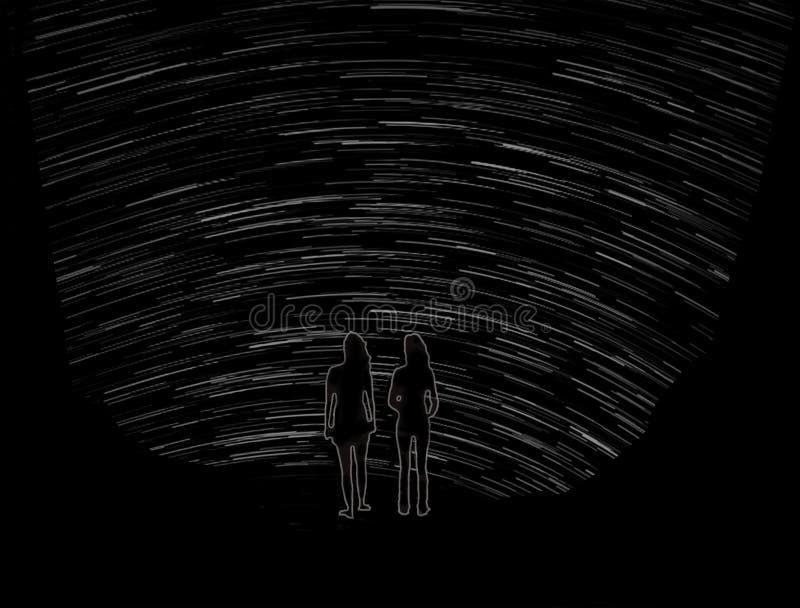 Δύο κορίτσια που στέκονται στο νυχτερινό ουρανό προσοχής ακρών απότομων βράχων στοκ εικόνες