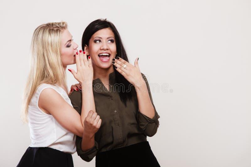 Δύο κορίτσια που ψιθυρίζουν και που χαμογελούν, κουτσομπολιό στοκ φωτογραφία με δικαίωμα ελεύθερης χρήσης