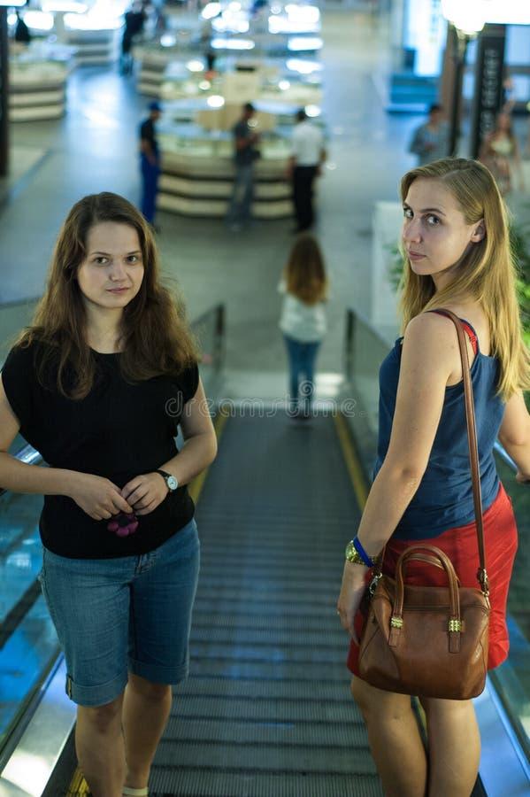 Δύο κορίτσια στην κυλιόμενη σκάλα στοκ φωτογραφία με δικαίωμα ελεύθερης χρήσης