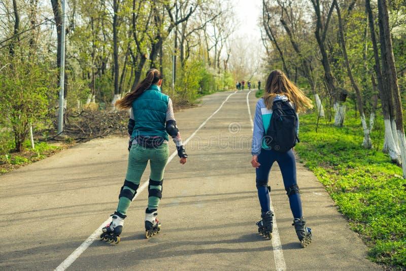 Δύο κορίτσια στο γύρο σαλαχιών κυλίνδρων κατά μήκος του δρόμου το ένα δίπλα στο άλλο στοκ φωτογραφία