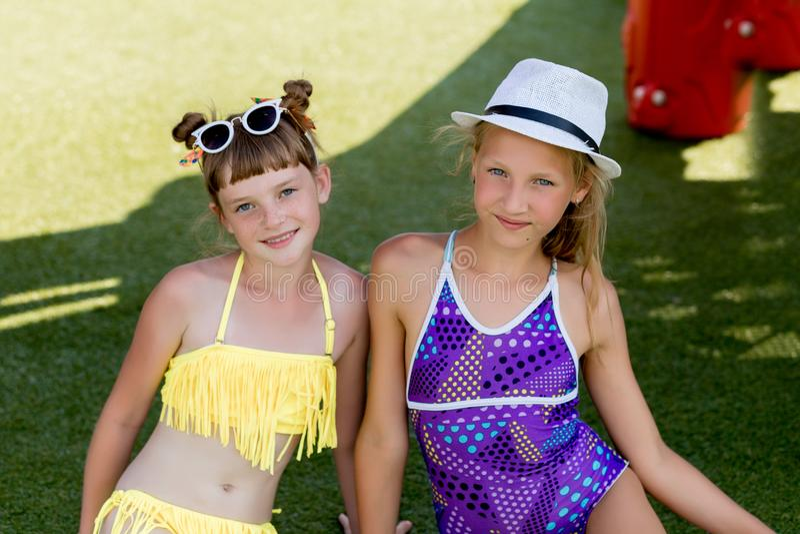 Δύο κορίτσια στο μαγιό έχουν τη διασκέδαση στη χλόη από τη λίμνη στοκ φωτογραφία
