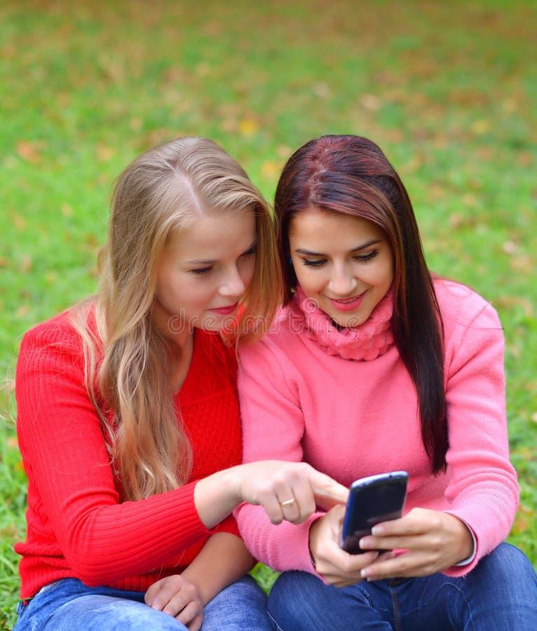 Δύο κορίτσια στο πάρκο με ένα κινητό τηλέφωνο το φθινόπωρο στοκ φωτογραφία με δικαίωμα ελεύθερης χρήσης