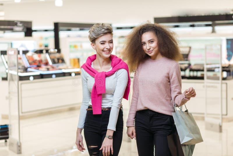 Δύο κορίτσια συναδέλφων καλύτερων φίλων που θέτουν στο σύγχρονο υπόβαθρο λεωφόρων αγορών στοκ φωτογραφία με δικαίωμα ελεύθερης χρήσης