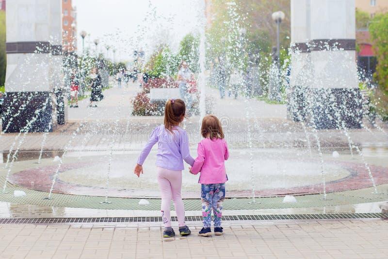 Δύο κορίτσια της αδελφής εξετάζουν την πηγή, ενώνοντας τα χέρια Περίπατος γύρω από την πόλη, άποψη από μια πλάτη στοκ φωτογραφίες με δικαίωμα ελεύθερης χρήσης